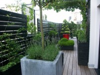 Aménagement d'une terrasse en bois, avec gros pots rouges