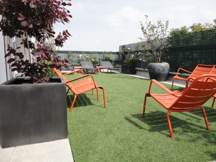 Aménagement terrasse parisienne avec mobilier orange Fermob