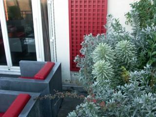 Aménagement végétal, avec mobilier gris anthracite et rouge