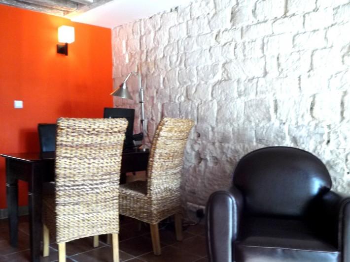 Bureau du cabinet immobilier avec un mur en pierres blanches