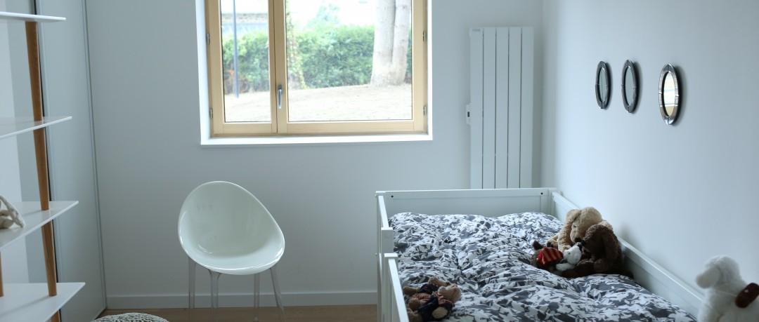 Chambre blanche avec lit pour enfant et radiateur mural