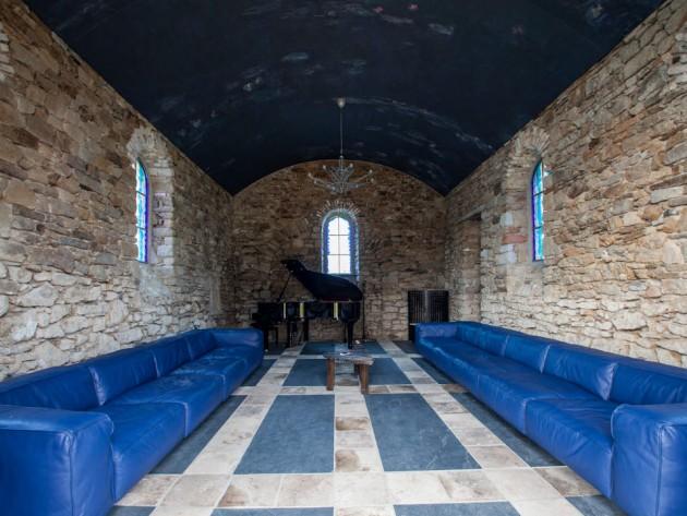 Chappelle réhabilitée en auditorium avec canapés en cuir bleu éléctrique