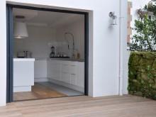 Cuisine contemporaine et ouverte sur une terrasse en bois