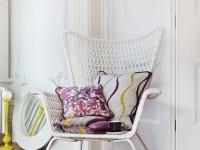 Fauteuil design en osier blanc ornée de coussins décoratifs