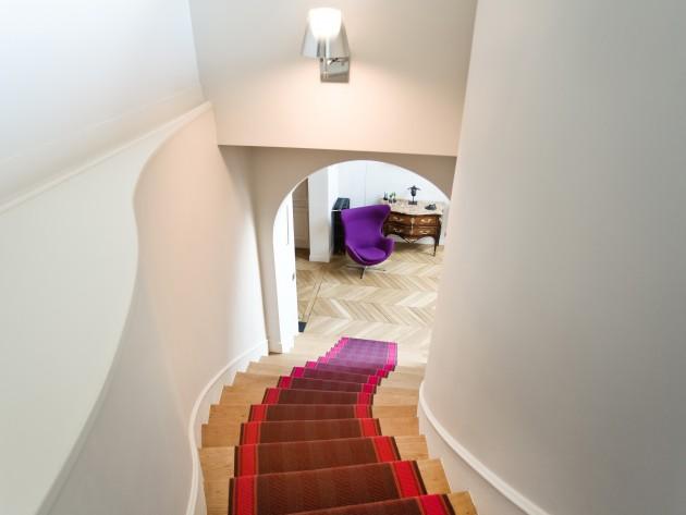 Grand escalier en bois avec tapis coloré
