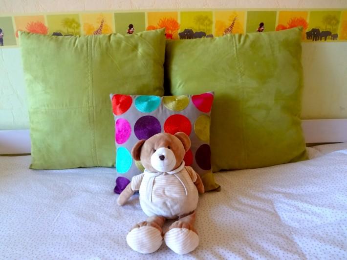 Lit dans la chambre d'enfant avec coussins vert anis