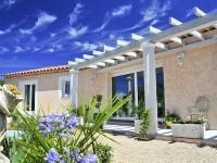 Maison individuelle avec pergola et terrasse entourant la maison