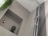 Niche décorative dans douche à l'italienne équipée d'un ciel de pluie