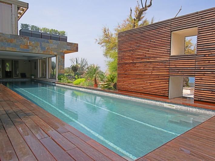 Piscine couloir de nage en partie recouverte par la maison