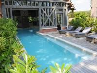 Piscine intérieure et extérieur avec terrasse en bois grisé