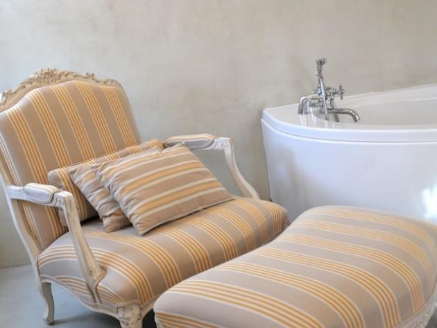 Salle de bains avec fauteuil et repose pied