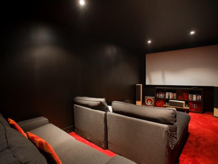 Salle de cinéma avec canapés en tissus gris et moquette rouge