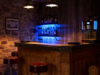 Salon avec bar en bois et en zinc avec hauts tabourets