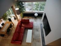Salon carrelage en pierre naturelle et canapé en cuir rouge